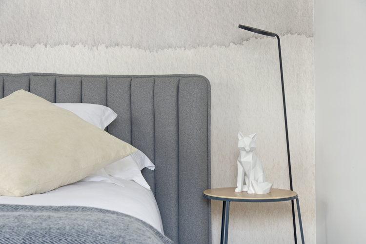 La tête du lit avec sa lampe de chevet