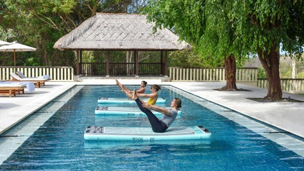 En équilibre via des postures de yoga sur un matelas sur l'eau