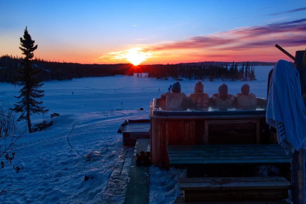Séance Jacuzzi en contemplant le coucher de soleil sur l'horizon blanc de neige